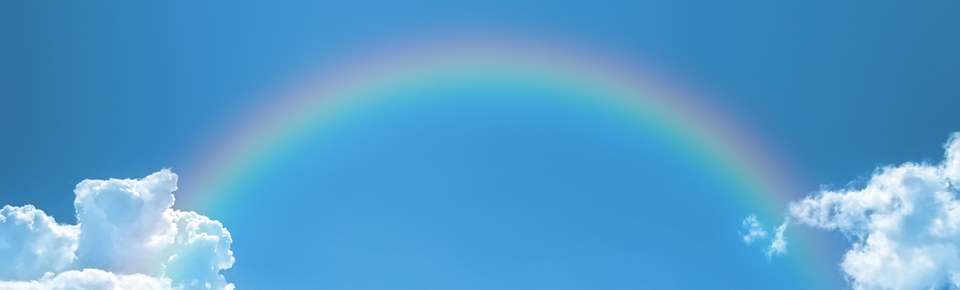 Rainbow arching between clouds